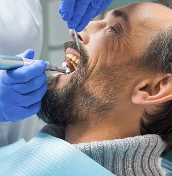 Dentist providing dentistry services for male patient