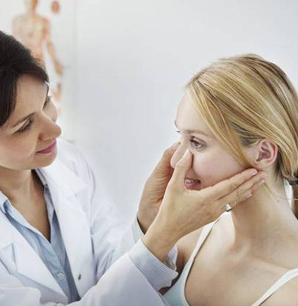 Dentist checking female patient's facial structures for swelling