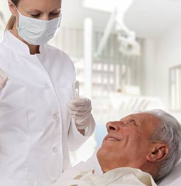 Dentist giving senior man the okay after oral cancer screening