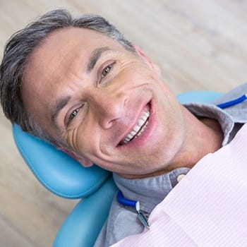 Man smiling in dental chair leaning back