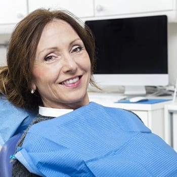 Woman smiling in dental chair looking at camera