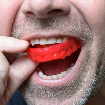 man with facial hair putting in mouthguard