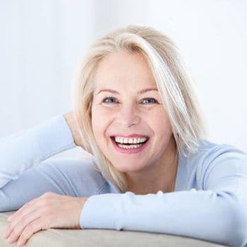 Older woman smiling after dental implant tooth replacement