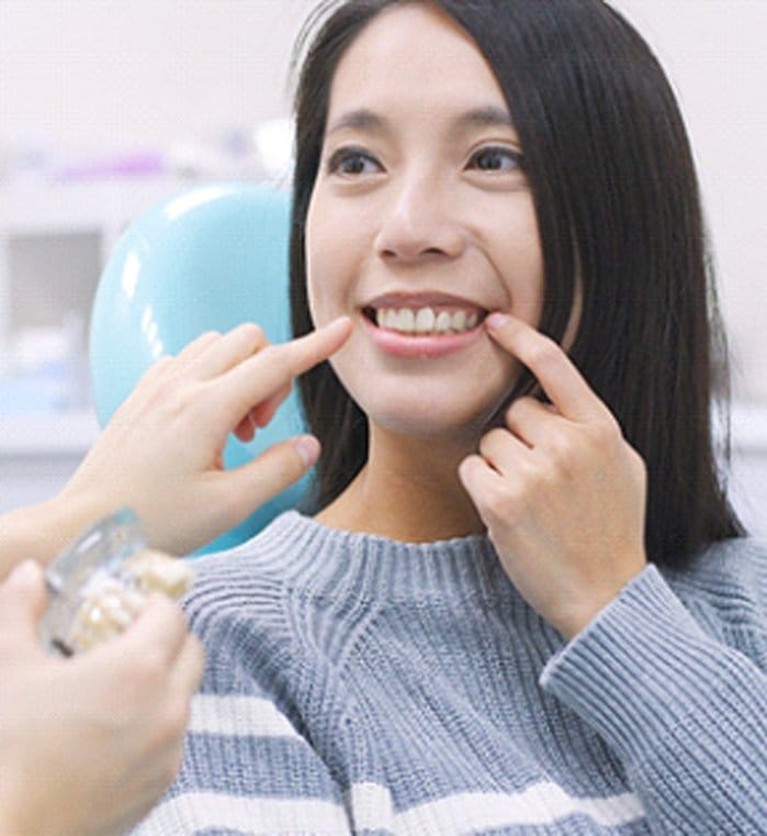A young female pointing to her teeth while a dentist also points to an area in which a dental implant in Greenwood would be beneficial