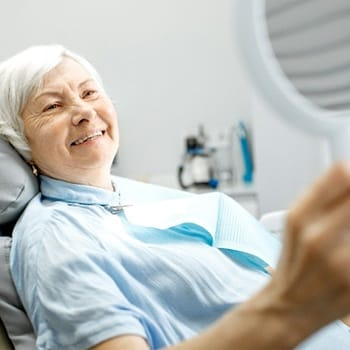 An older woman lying back in a dentist's chair and admiring her new smile in a handheld mirror