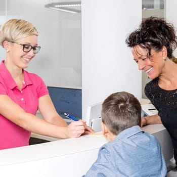 A dental receptionist explaining the cost of dental implant treatment with a mom and her two children