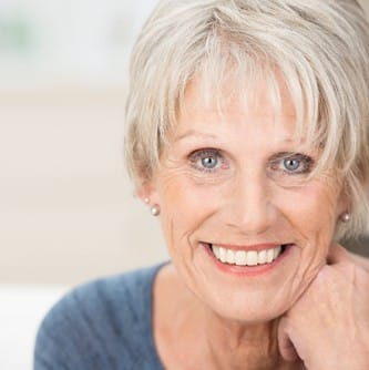 woman smiling after implant supported bridge placement