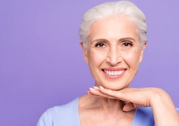 An older woman holds her hand below her chin and smiles, showing off her new dentures
