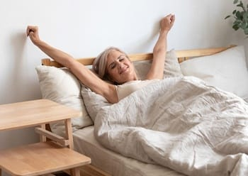 An older woman stretching after waking from a restful night's sleep