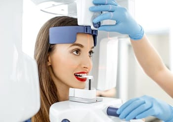 A woman standing at the Conebeam/CT 3D scanner while a dental assistant assists
