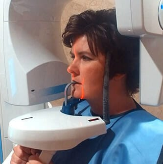 Woman receiving x-ray scan during emergency dentistry visit
