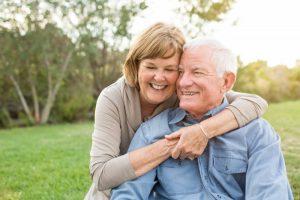 older couple smiling hugging