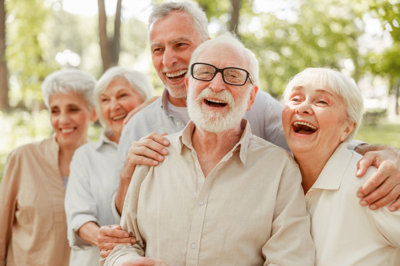 a group of older individuals showing off their new dental implants in Simpsonville